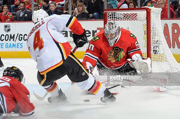 Kris Russell of the Calgary Flames attempts to put the puck past goalie Corey Crawford of the Chicago Blackhawks during the NHL game on October 15...