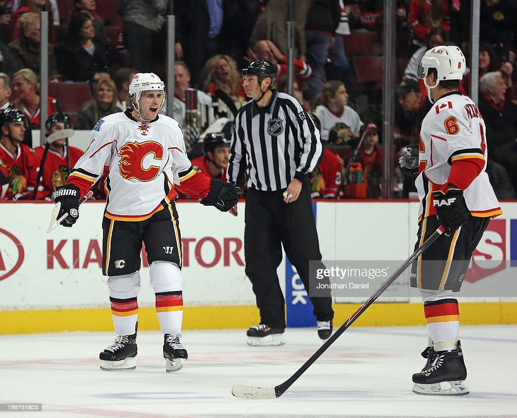 Kris Russell #4 of the Calgary Flames celebrates his game-winning overtime goal with Dennis Wideman #6 against the Chicago Blackhawks at the United Center on November 3, 2013 in Chicago, Illinois. The Flames defeated the Blackhawks 3-2 in overtime.