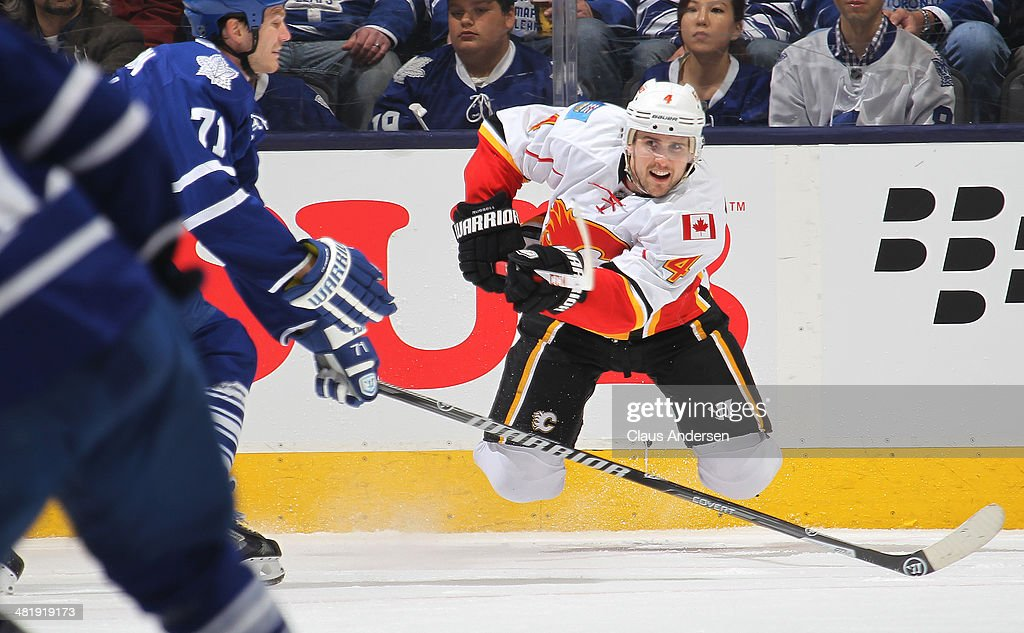 Kris Russell #4 of the Calgary Flames clears a puck against the Toronto Maple Leafs during an NHL game at the Air Canada Centre on April 1, 2014 in Toronto, Ontario, Canada. The Leafs defeated the Flames 3-2.