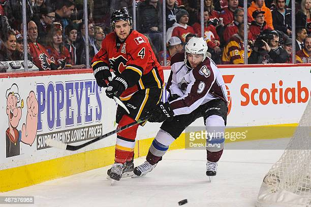 Kris Russell of the Calgary Flames fights for the puck against Matt Duchene of the Colorado Avalanche during an NHL game at Scotiabank Saddledome on...