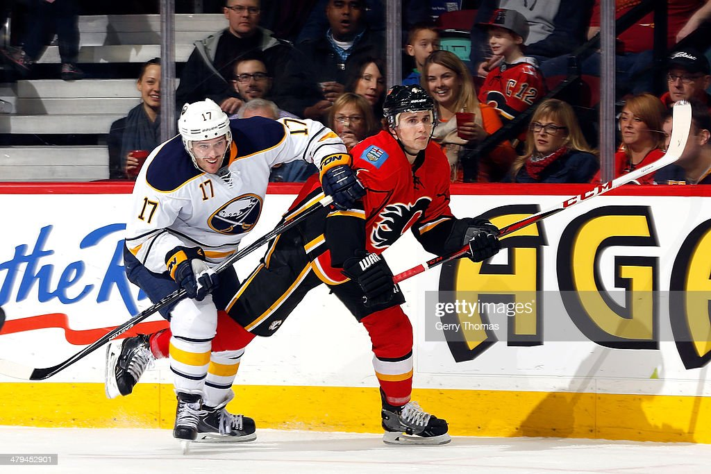 Kris Russell #4 of the Calgary Flames skates against Torrey Mitchell #17 of the Buffalo Sabres at Scotiabank Saddledome on March 18, 2014 in Calgary, Alberta, Canada.
