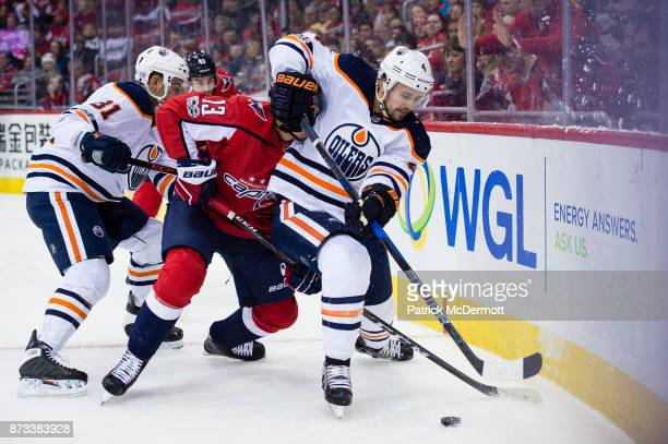 Kris Russell of the Edmonton Oilers and Jakub Vrana of the Washington Capitals battle for the puck in the first period at Capital One Arena on...