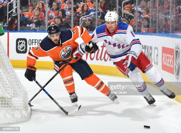Kris Russell of the Edmonton Oilers battles for the puck against Cody McLeod of the New York Rangers on March 3 2018 at Rogers Place in Edmonton...