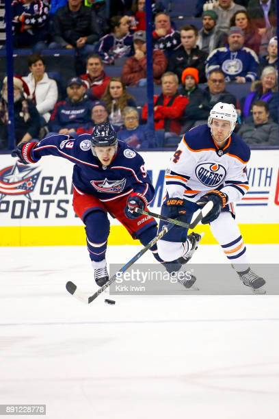 Kris Russell of the Edmonton Oilers skates the puck up ice away from Artemi Panarin of the Columbus Blue Jackets during the first period on December...
