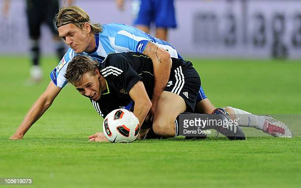 Kris Stadsgaard of Malaga falls on top of Sergio Canales of Real Madrid during the La Liga match between Malaga and Real Madrid at La Rosaleda...