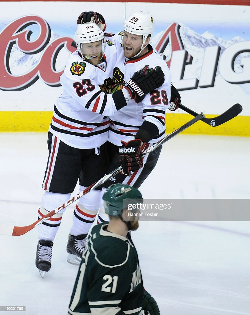 Kris Versteeg #23 and Bryan Bickell #29 of the Chicago Blackhawks celebrate a goal by Versteeg as Kyle Brodziak #21 of the Minnesota Wild looks on during the first period in Game Six of the Second Round of the 2014 NHL Stanley Cup Playoffs on May 13, 2014 at Xcel Energy Center in St Paul, Minnesota.