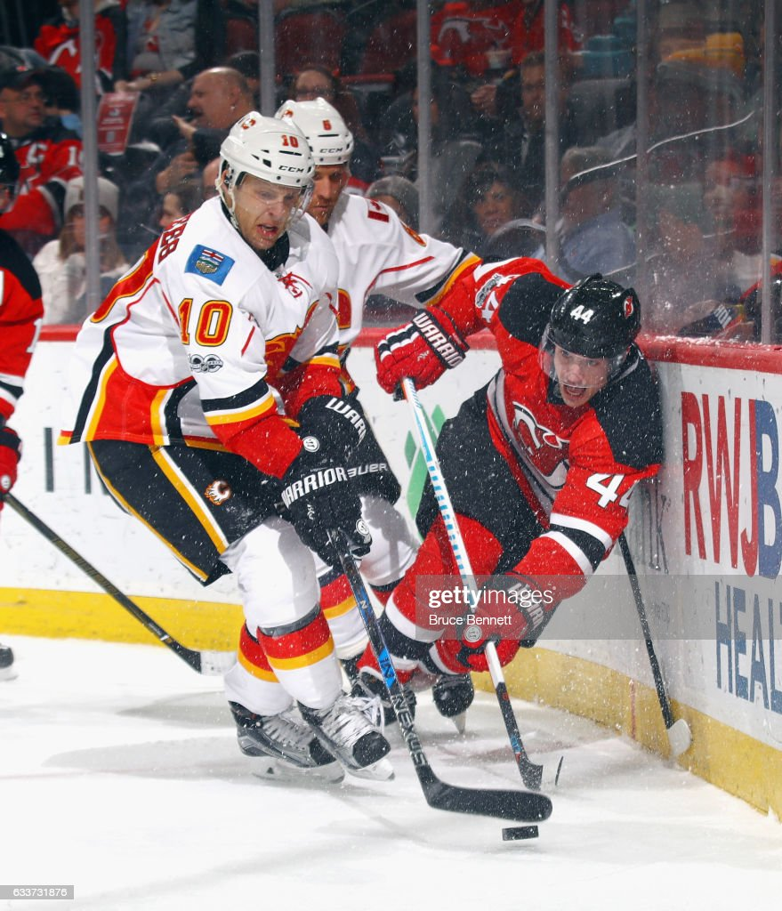 Kris Versteeg #10 of the Calgary Flames and Miles Wood #44 of the New Jersey Devils battle for the puck during the second period at the Prudential Center on February 3, 2017 in Newark, New Jersey.