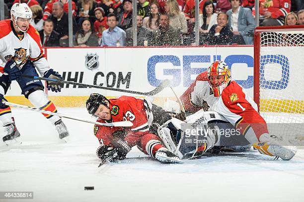 Kris Versteeg of the Chicago Blackhawks collides into goalie Roberto Luongo of the Florida Panthers as Aleksander Barkov skates in from the side...
