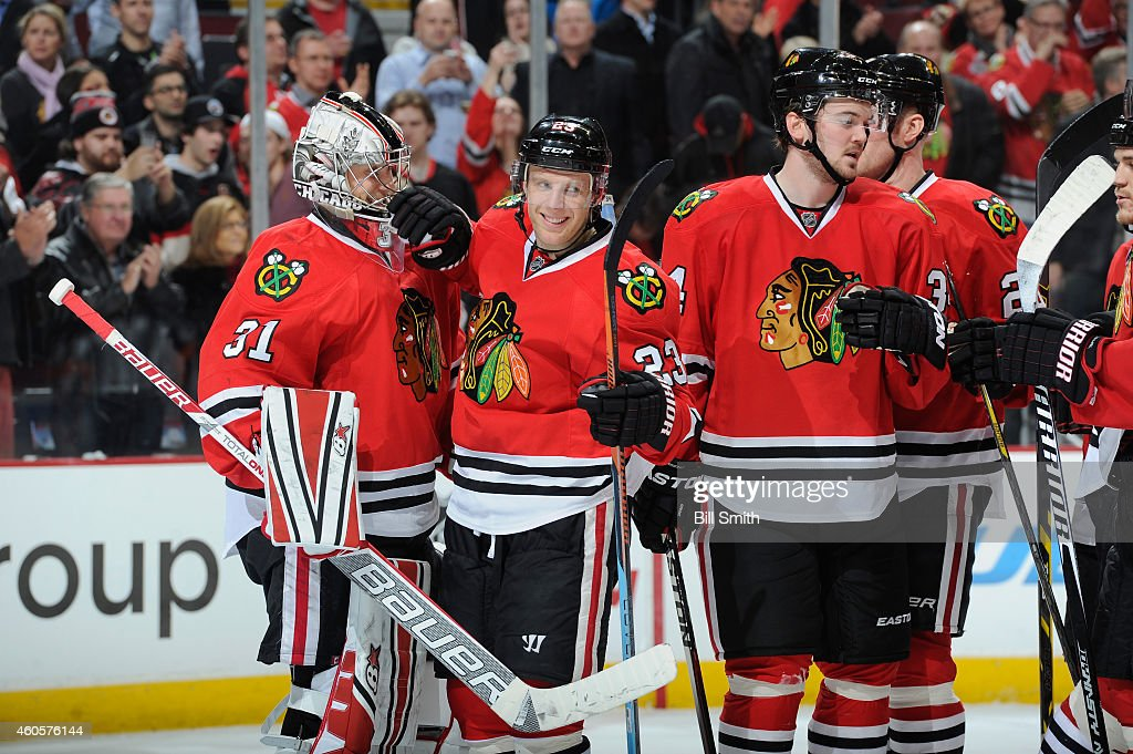 Kris Versteeg #23 of the Chicago Blackhawks congratulates goalie Antti Raanta #31 after a 5-3 win against the Minnesota Wild during the NHL game at the United Center on December 16, 2014 in Chicago, Illinois.