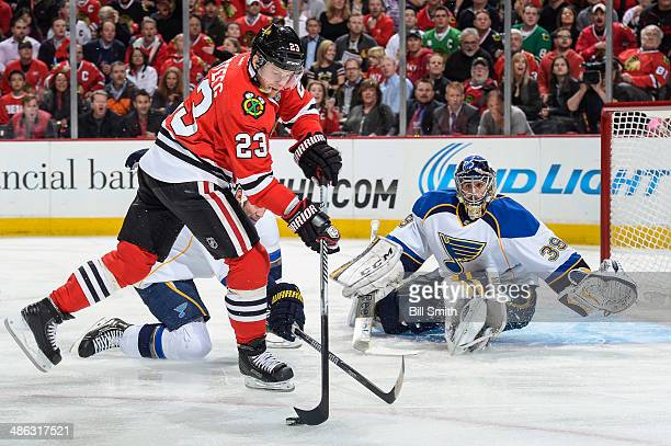 Kris Versteeg of the Chicago Blackhawks grabs the puck next to goalie Ryan Miller of the St Louis Blues in Game Four of the First Round of the 2014...
