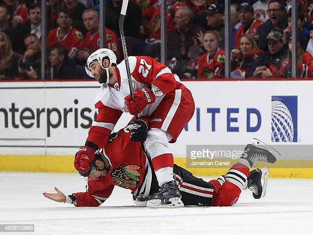 Kris Versteeg of the Chicago Blackhawks is held to the ice by Kyle Quincey of the Detroit Red Wings at the United Center on February 18 2015 in...