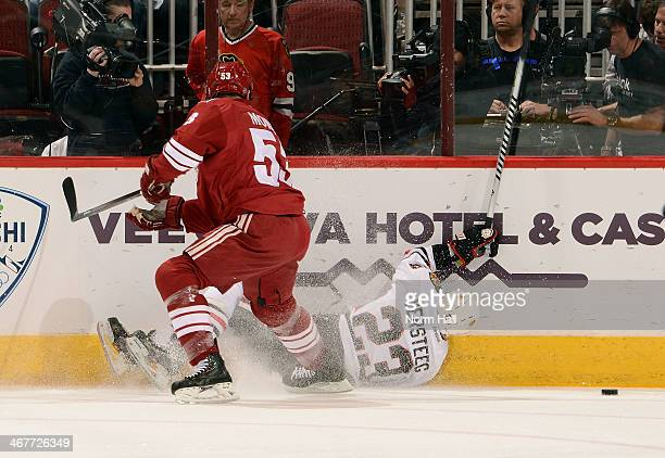 Kris Versteeg of the Chicago Blackhawks loses control of the puck while falling to the ice as Derek Morris of the Phoenix Coyotes defends during the...