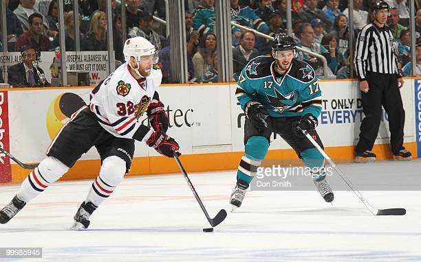 Kris Versteeg of the Chicago Blackhawks moves the puck around Torrey Mitchell of the San Jose Sharks in Game One of the Western Conference Finals...