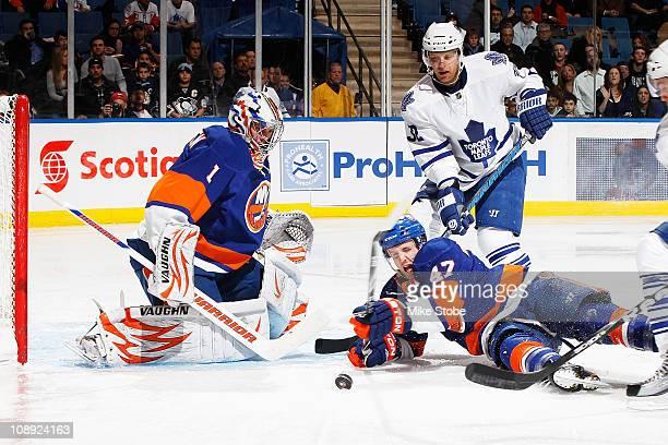 Kris Versteeg of the Toronto Maple Leafs takes a shot as Goaltender Mikko Koskinen of the New York Islanders watches as teammate Andrew MacDonald...