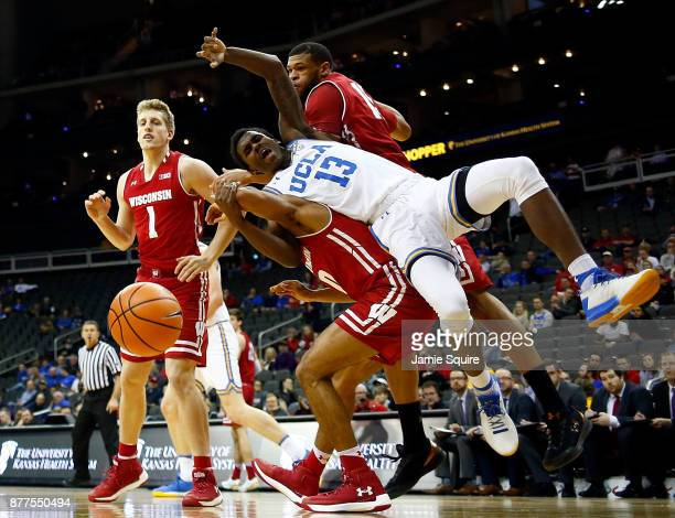 Kris Wilkes of the UCLA Bruins falls over D'Mitrik Trice of the Wisconsin Badgers while competing for a rebound during the National Collegiate...