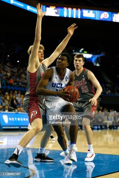 Kris Wilkes of the UCLA Bruins looks for an opening under the hoop as Jayce Johnson of the Utah Utes and Riley Battin of the Utah Utes try to block...