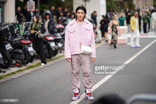 Kris Wu wears earrings pink sunglasses necklaces a pink knit jacket a pink top a white Louis Vuitton bag dusty pink pants Louis Vuitton sneakers...