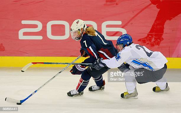 Krissy Wendell of the United States and Saara Tuominen of Finland fight for the puck during the women's ice hockey bronze medal match during Day 10...