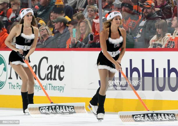 Krista Allysse Cipollone and Kristen Mee of the Philadelphia Flyers ice girls clean the ice during a timeout against the Boston Bruins on December 2...