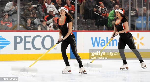Krista Allysse Cipollone and Lexi Lord of the Philadelphia Flyers ice girls clean the ice during a timeout against the Buffalo Sabres on December 19...