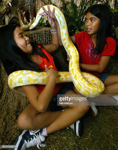 Krista Bathan left, and her sister Risha from Santa Clarita, are greeted by Sunny, a female Albino Burmese Python that is 1 and 1/2 years old. The...