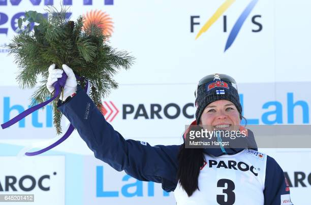 Krista Parmakoski of Finland poses during the flower ceromeny after winning a silver medal in the Women's Cross Country Skiathlon during the FIS...