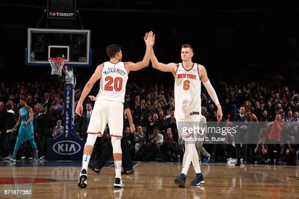 Kristaps Porzingis high fives Doug McDermott of the New York Knicks during the game against the Charlotte Hornets on November 7 2017 at Madison...