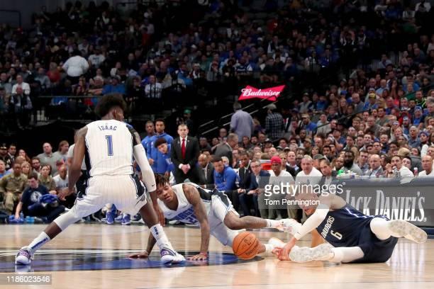 Kristaps Porzingis of the Dallas Mavericks scrambles for the ball against Jonathan Isaac of the Orlando Magic and Markelle Fultz of the Orlando Magic...