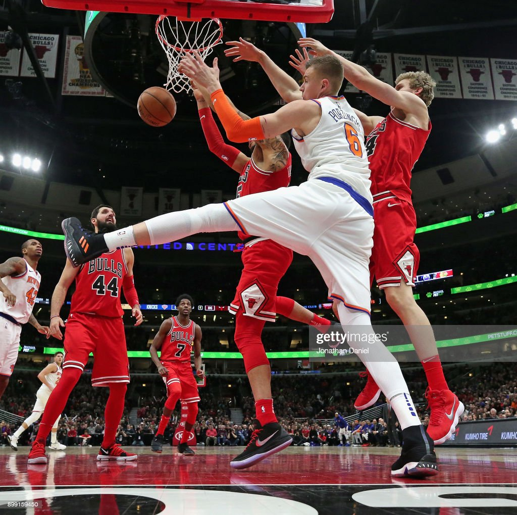 Kristaps Porzingis #6 of the New York Knicks battles for a rebound with Denzel Valentine #45 and Luari Markkanen #24 (R) of the Chicago Bulls at the United Center on December 27, 2017 in Chicago, Illinois. The Bulls defeated the Knicks 92-87.