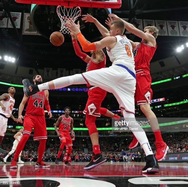 Kristaps Porzingis of the New York Knicks battles for a rebound with Denzel Valentine and Luari Markkanen of the Chicago Bulls at the United Center...