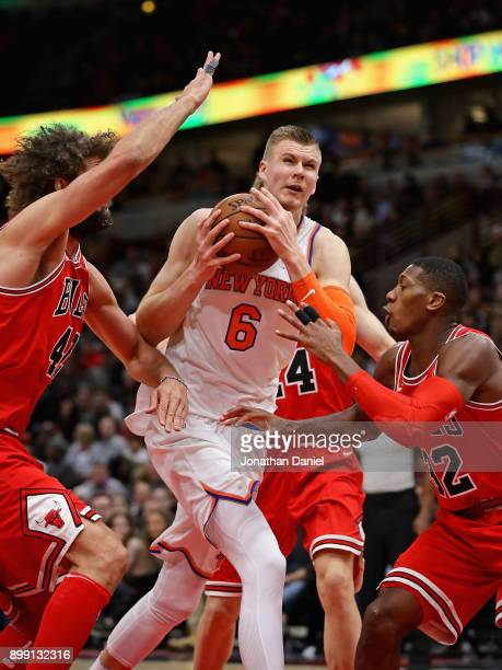 Kristaps Porzingis of the New York Knicks drives between Robin Lopez and Kris Dunn of the Chicago Bulls at the United Center on December 27 2017 in...