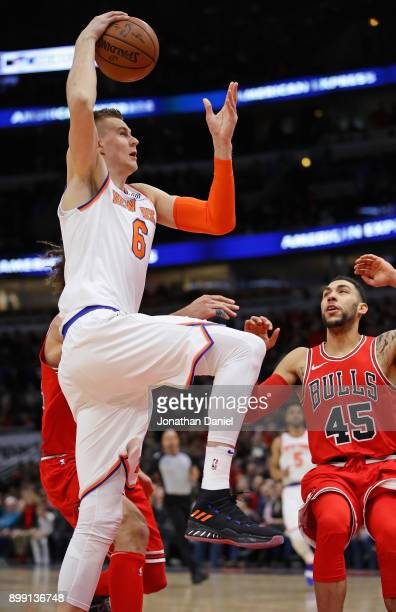 Kristaps Porzingis of the New York Knicks goes up for a dunk against Robin Lopez and Denzel Valentine of the Chicago Bulls at the United Center on...