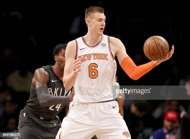 Kristaps Porzingis of the New York Knicks grabs the ball as Rondae HollisJefferson of the Brooklyn Nets defends at the Barclays Center on December 14...