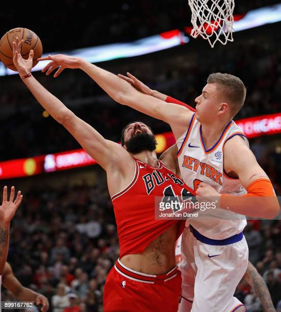 Kristaps Porzingis of the New York Knicks grabs the jersey of Nikola Mirotic of the Chicago Bulls as they battle for a rebound at the United Center...