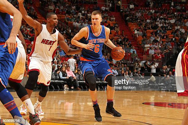 Kristaps Porzingis of the New York Knicks handles the ball against Chris Bosh of the Miami Heat on January 6 2016 at American Airlines Arena in Miami...