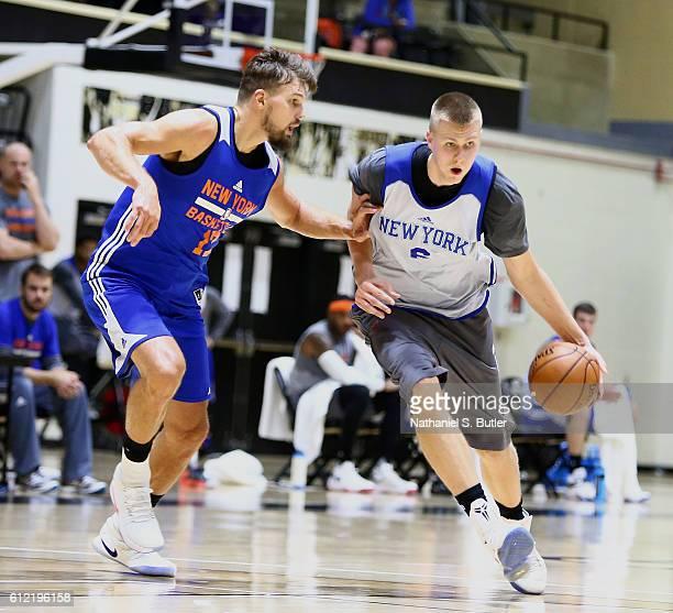 Kristaps Porzingis of the New York Knicks handles the ball against Lou Amundson of the New York Knicks during training camp practice on September 30...