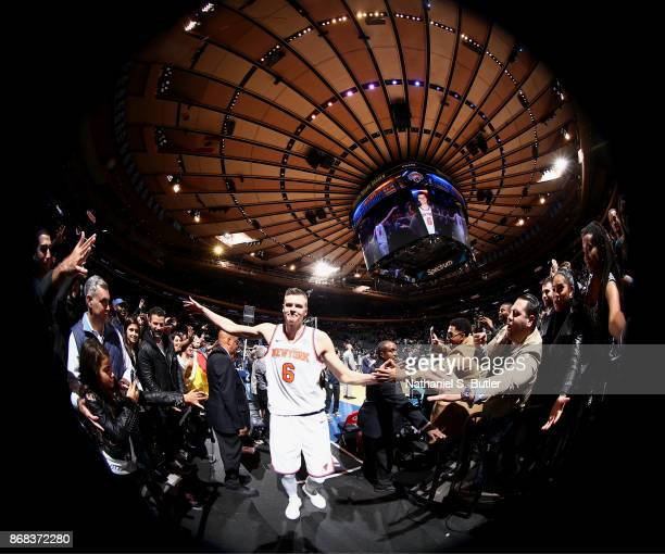 Kristaps Porzingis of the New York Knicks high fives fans after the game against the Denver Nuggets on October 30 2017 at Madison Square Garden in...