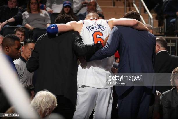 Kristaps Porzingis of the New York Knicks is carried off court after tearing his ACL in his left knee during the game against the Milwaukee Bucks on...