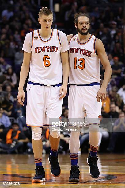 Kristaps Porzingis of the New York Knicks is congratulated by Joakim Noah after scoring against the Phoenix Suns during the first half of the NBA...