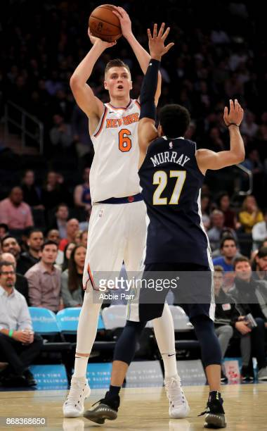 Kristaps Porzingis of the New York Knicks looks to take a shot against Jamal Murray of the Denver Nuggets in the fourth quarter during their game at...
