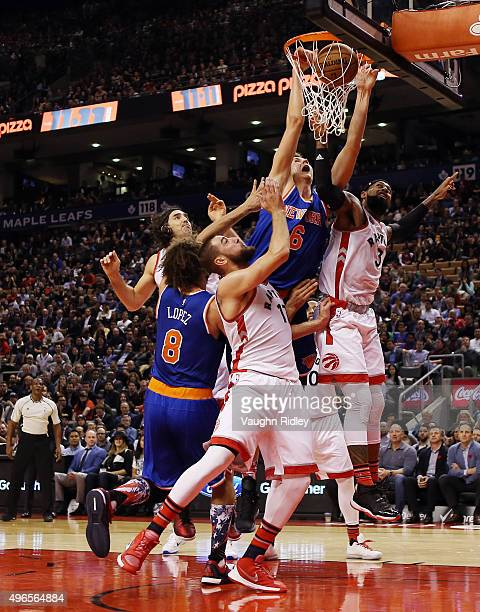Kristaps Porzingis of the New York Knicks scores as Jonas Valanciunas and James Johnson of the Toronto Raptors defend during an NBA game at the Air...