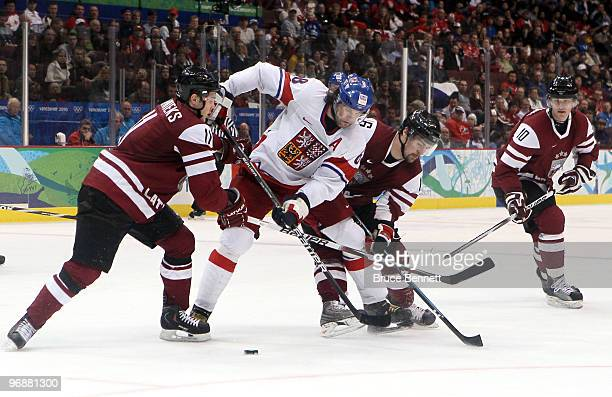 Kristaps Sotnieks and Kaspars Daugavins of Latvia challenge Jaromir Jagr of Czech Republic for the puck during the ice hockey men's preliminary game...