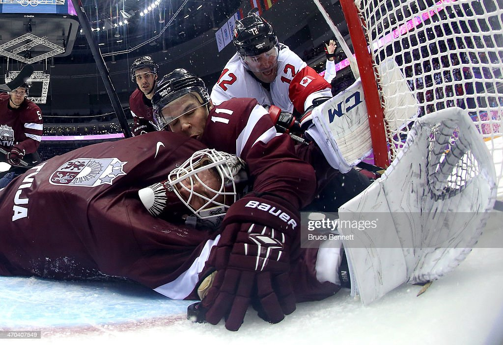 Kristaps Sotnieks #11 of Latvia reaches over goalkeeper Kristers Gudlevskis #50 for the puck during the third period of the Men's Ice Hockey Quarterfinal Playoff against Canada on Day 12 of the 2014 Sochi Winter Olympics at Bolshoy Ice Dome on February 19, 2014 in Sochi, Russia.