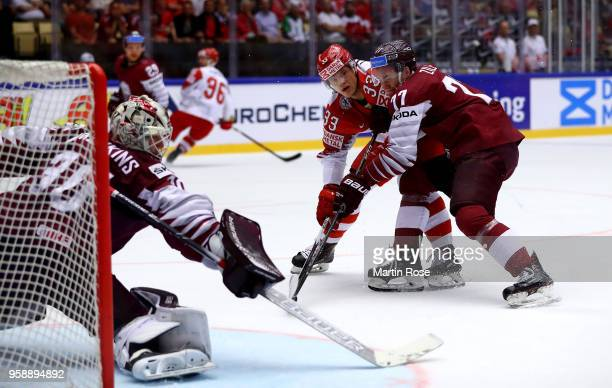 Kristaps Zile of Latvia and Julian Jakobsen of Denmark battle for the puck during the 2018 IIHF Ice Hockey World Championship Group B game between...
