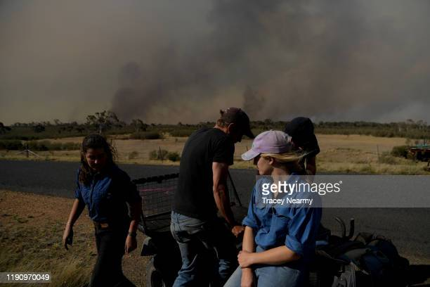 Kristen Amicair and Mick Mason of Mick Mason's Horses keep watch over their property and livestock as firefighter battle to contain spot fires near...
