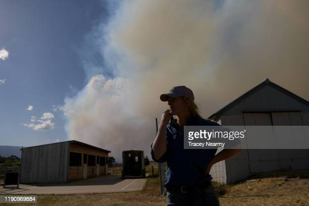 Kristen Amicair of Mick Mason's Horses keep watch over their property and livestock as firefighter battle to contain spot fires near the Tallaganda...
