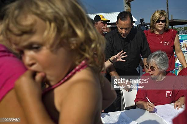 Kristen Campo rests on her mother's shoulder as Father John Arnone speaks with representatives of Catholic Charities at the Breton Sound Marina May 5...