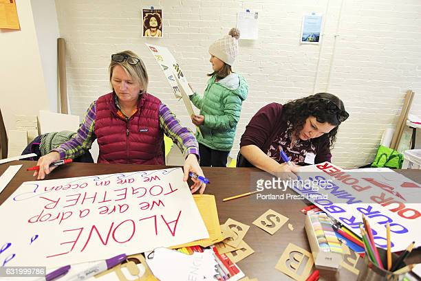 Kristen Farnham left and her daughter Audrey of Falmouth work alongside Beth Penrose of Cumberland as people gather at 24 Preble Street to make signs...
