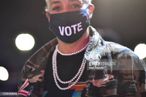 """Kristen Hart wears a """"VOTE"""" mask before Democratic vice presidential nominee Sen. Kamala Harris speaks at a drive-in election eve rally on November..."""
