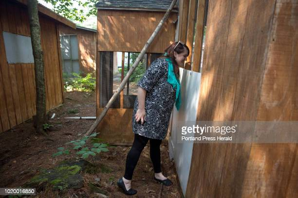 Kristen Lamb executive director at the Center for Wildlife peaks in to a porcupine's cage at the Center for Wildlife on Thursday August 16 2018 Last...